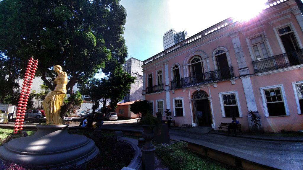 Fotografia da fachada da escola, na contra-luz, com o sol iluminando as esculturas do jardim.