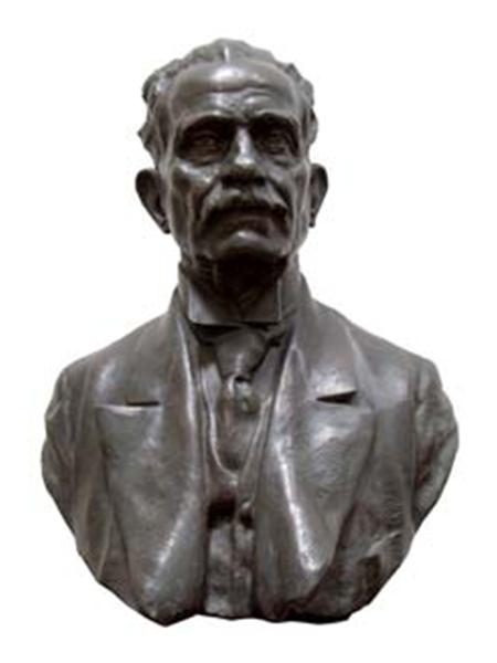 Fotografia da escultura em aço, na qual o representado aparece com expressão séria, calvo, em traje a rigor.