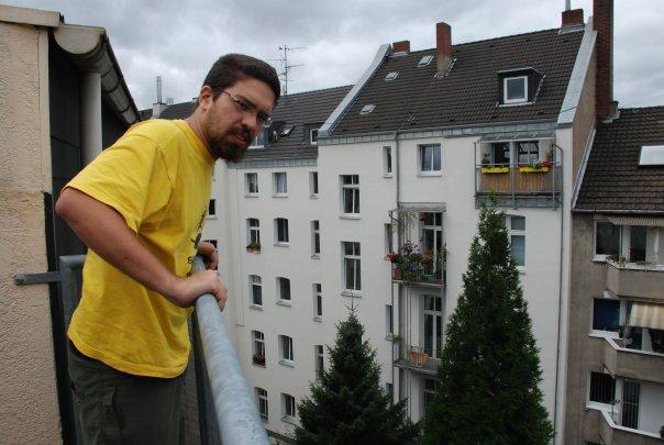 Retrato do professor, em plano médio, com expressão séria, pele branca, cabelos e barba pretos, óculos de grau, de camiseta amarela, na varanda de um prédio com janelas e telhados ao fundo.