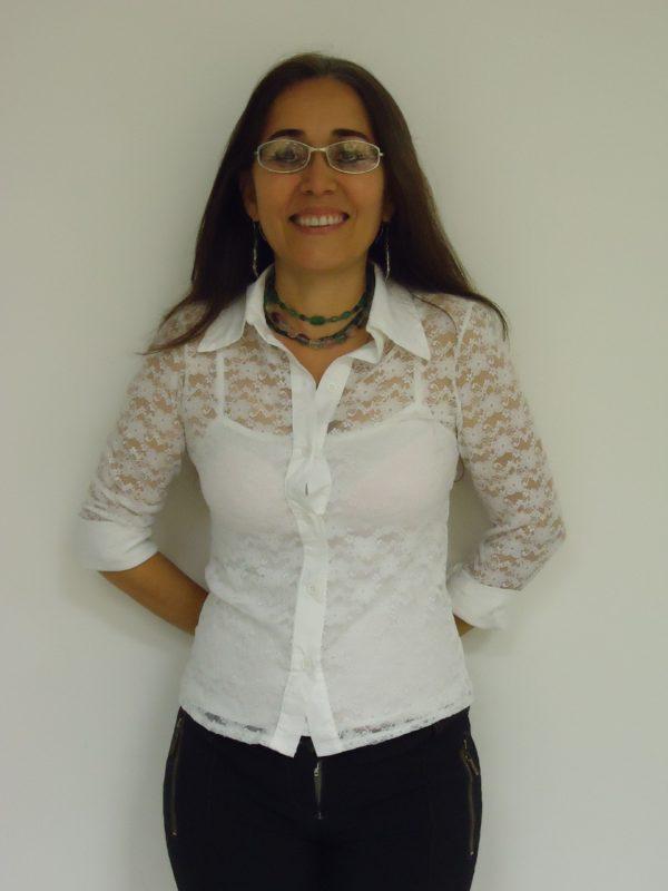 Retrato da professora sorridente em plano americano, pele clara, cabelos lisos longos, óculos de grau, colar de pedras grandes e coloridas, blusa branca de manga comprida de renda sobre um top branco e calça jeans.