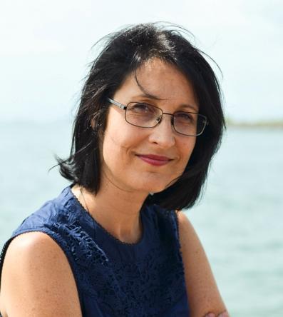 Retrato da professora, sorridente, pele branca, cabelos pretos lisos até o pescoço, óculos de grau, veste blusa azul sem mangas, com o mar ao fundo.