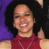 Retrato 3x4 da professora com expressão sorridente, pele negra, cabelos cacheados, blusa vermelha sem mangas e corrente fina de ouro