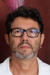 Retrato 3 por 4 do professor sério, pele branca, cabelos pretos curtos, óculos de grau, barba e bigode grisalhos e vestindo camisa branca
