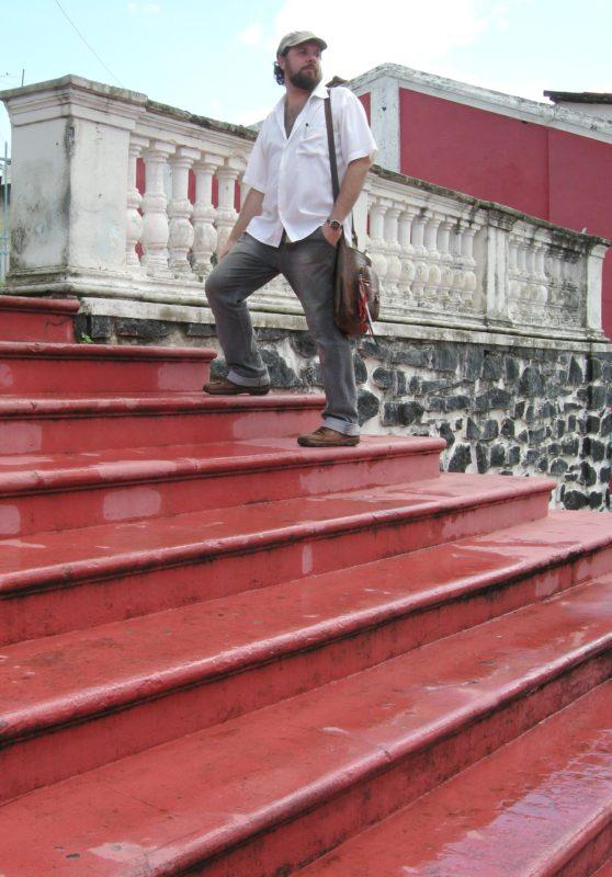 Retrato do professor em pé numa escadaria vermelha. O professor, pele branca, barba e bigode, veste calça jeans, camisa branca, botas marrom, bolsa a tiracolo e boné.