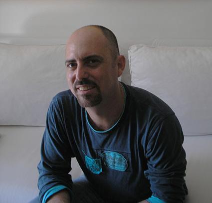 Retrato do professxor sorrindo, sentado, pele clara, cabelo raspado, barba e cavanhaque, camisa azul de manda comprida