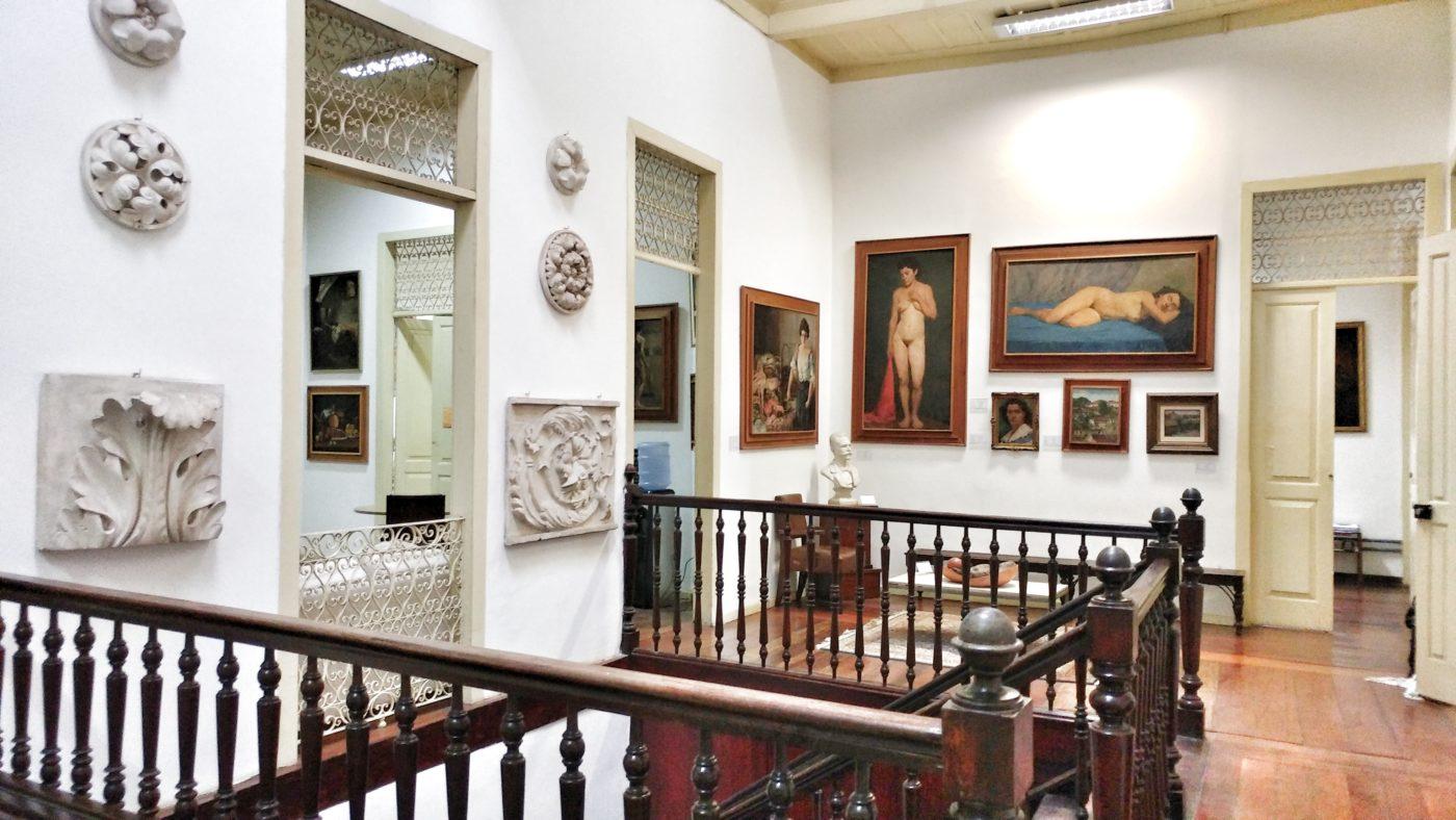 Fotografia do primeiro andar do casarão, com vista dos corrimãos da escada e dos quadros nas paredes.